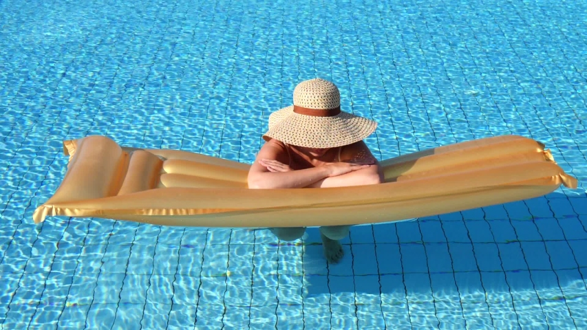 A young girl in beige straw hat with wide brim and in swimsuit, one swims in pool with blue turquoise water on golden air mattress, top view. Summer vacation, relaxation in pool. Slow motion video.   Shutterstock HD Video #1055075117