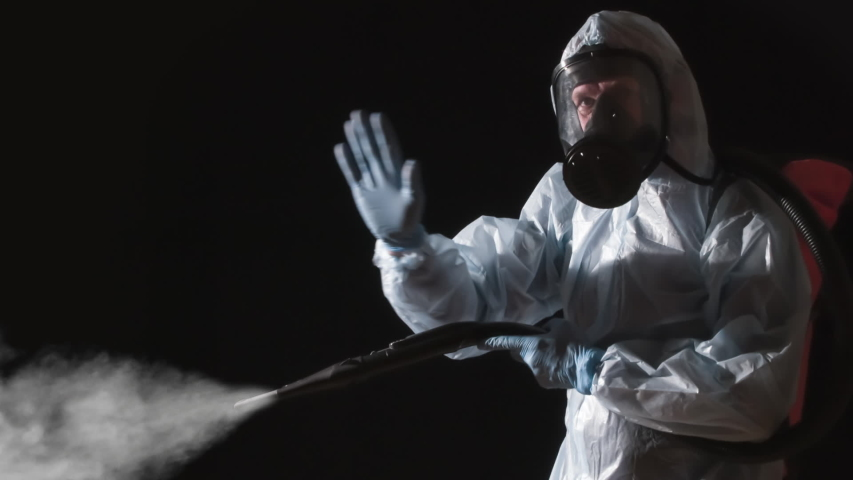 Caution Disinfection is in Progress. A man in a protective suit, glasses and a respirator sprays a disinfectant. At the same time, he makes gestures symbolizing the ban on presence Royalty-Free Stock Footage #1055076077