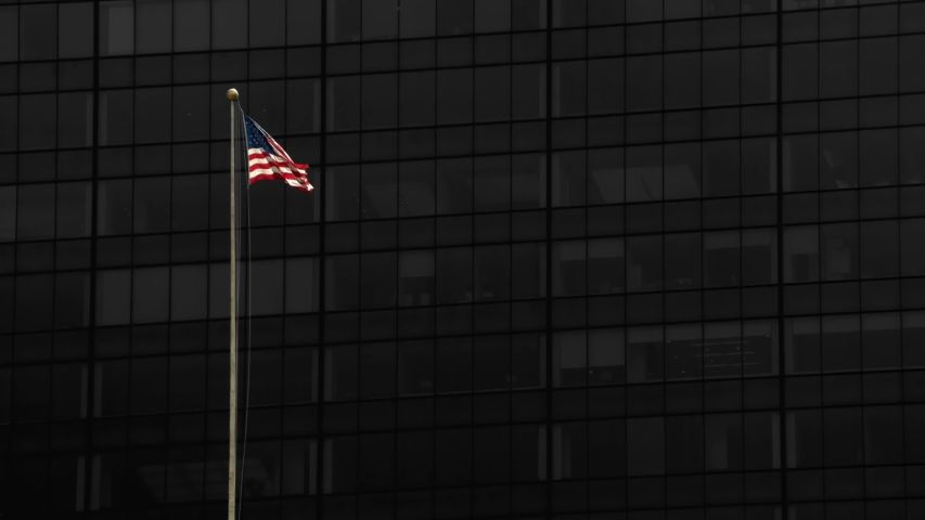 American Flag blowing in the wind with a dark building background. USA American flag waving United States of America. 4K 60P Manhattan New York City. USA flag on flagpole.