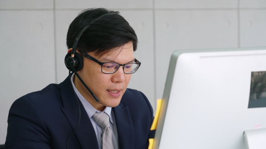 Business people wearing headset working in office to support remote customer or colleague. Call center, telemarketing, customer support agent provide service on telephone video conference call. | Shutterstock HD Video #1055079542