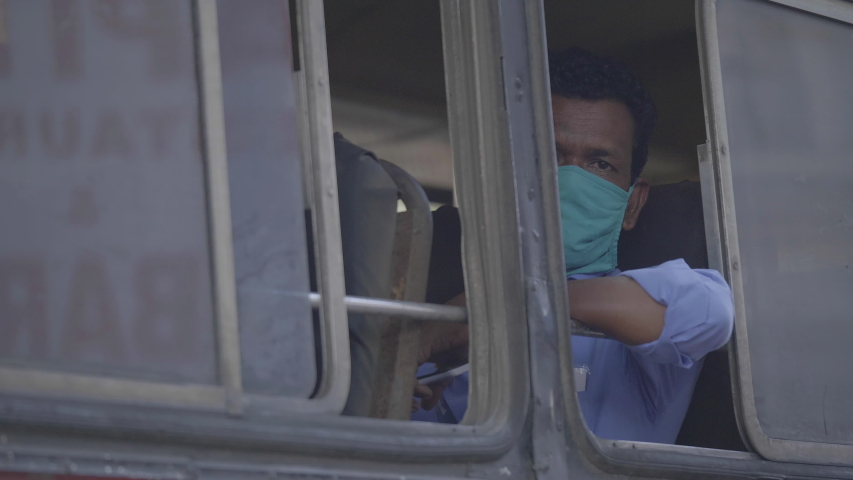 A man wearing face protective mask sitting in the bus and looking outside amid Corona virus or COVID 19 epidemic or pandemic, Mumbai, India (June 2020)