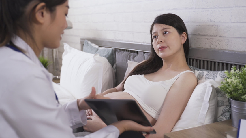 Asian lady with her doctor signing on tablet showing understanding of everything she needs to know during certain period of pregnancy. technology and modern medical care.