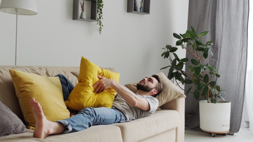 Young adult Caucasian man feeling bored staying at home during quarantine time lying on sofa playing yellow pillow Royalty-Free Stock Footage #1055083958