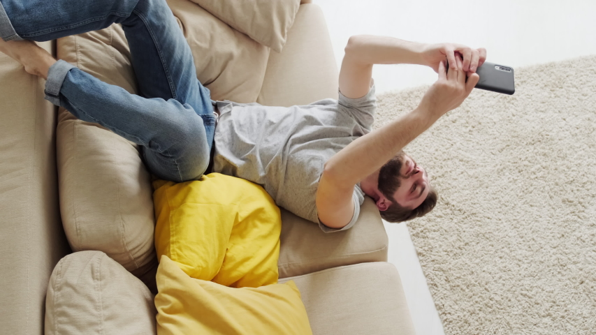 Bearded man lying on sofa upside down playing video game on his smartphone then getting bored and putting his gadget away, lockdown concept