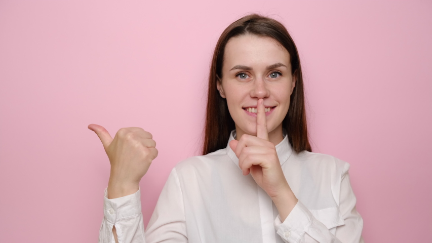 Cheerful young woman point with the finger at blank copy space aside, happy brunette girl make hush be a quiet gesture. tell about show secret sale offer, dressed in white shirt, isolated on pink background | Shutterstock HD Video #1055086493