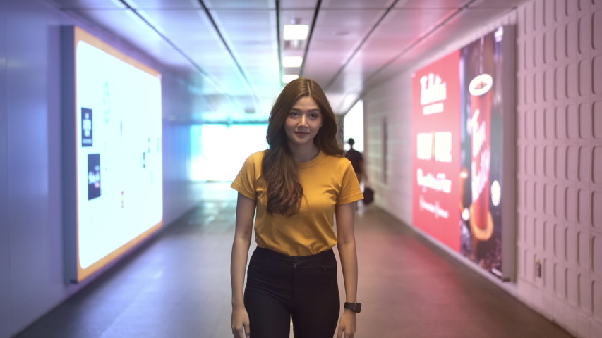 HD Slow motion smiling young beautiful long hair Asian woman walking forward with crowd people in subway station with neon lights. City lifestyle concept.  | Shutterstock HD Video #1055088404