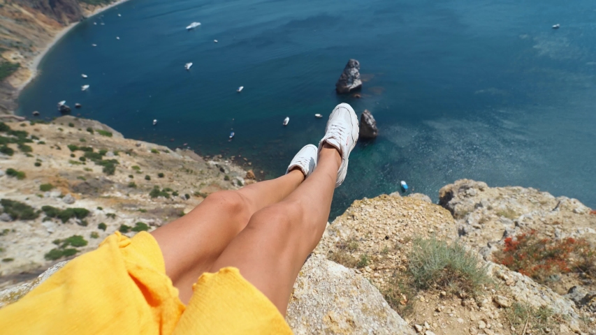 Camera zooming out first person view of taned woman legs in yellow dress sitting on on cliff edge. amazing nature view of seascape with high limestone cliff over blue sea and clear deep blue sky | Shutterstock HD Video #1055089256