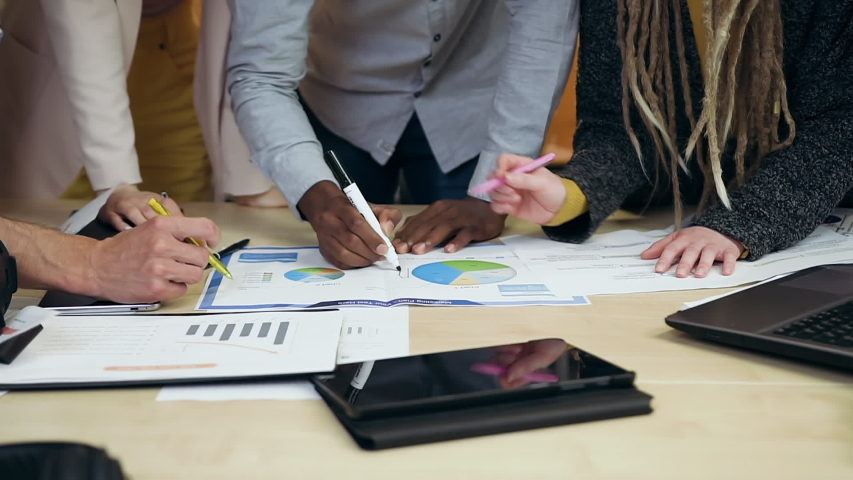 Close view of unrecognizable experienced young multiethnic men and women which standing near work table and planning business strategy of their project using financial diagramms   Shutterstock HD Video #1055091758