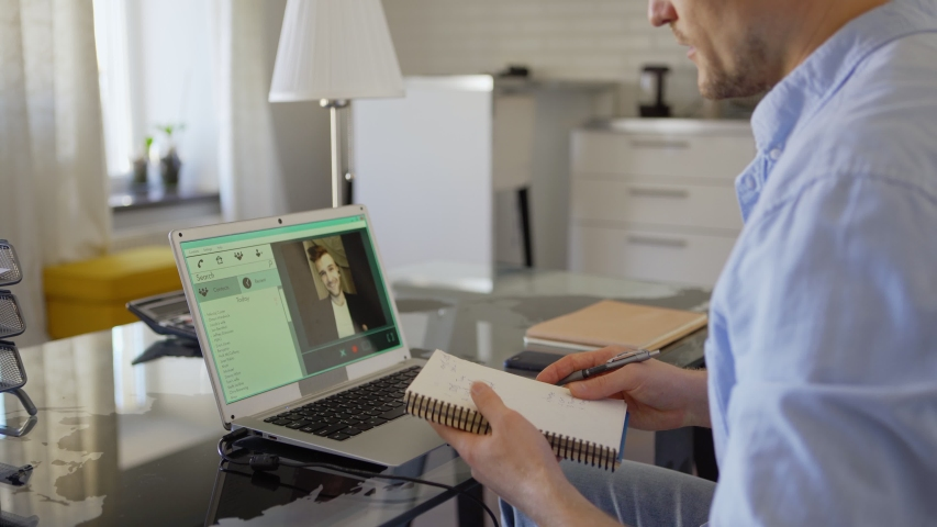 Zoom out side view shot of businessman taking notes in notepad while having video call with business partner on laptop computer. Man finishing online meeting, closing pc, reviewing notes and thinking