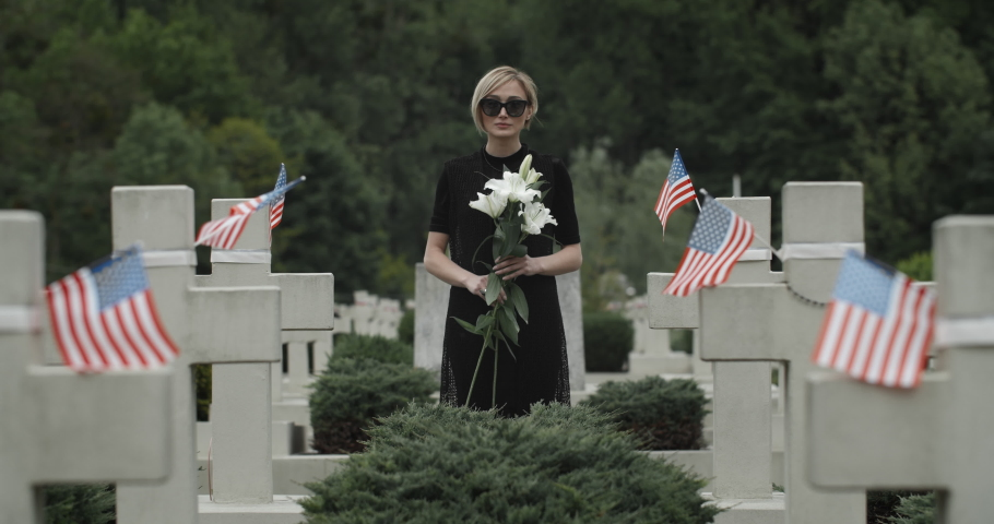 Portrait of woman holding white lily flower at cemetery. Widow in dark glasses looking to camera while standing in row of stone crosses with american flags. Concept of memorial day.