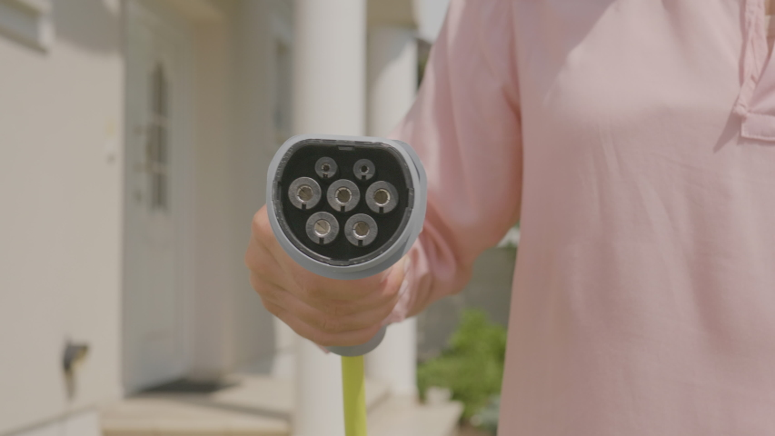 A woman covering the camera with a plug that charges electric cars Royalty-Free Stock Footage #1055094359