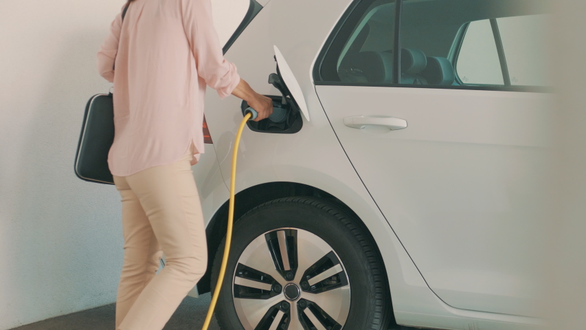 Shot of a woman walking up to her electric vehicle, plugging it in to charge on the parking lot Royalty-Free Stock Footage #1055094380