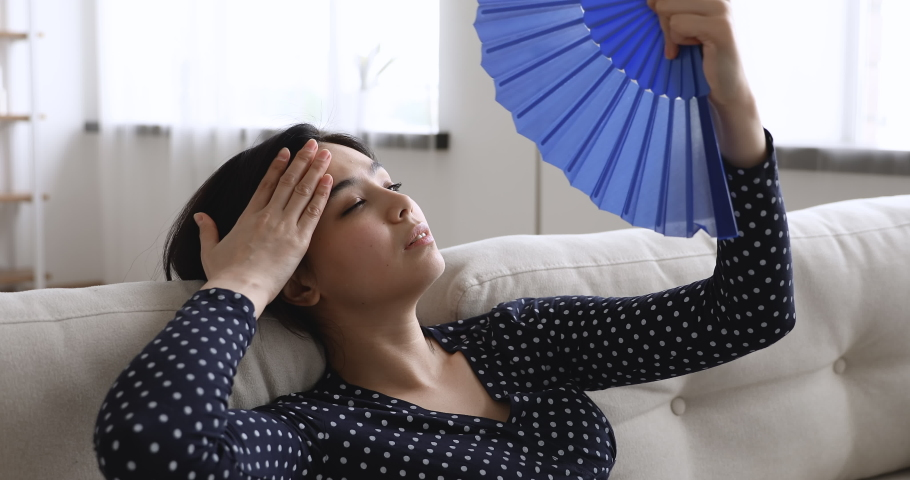 Close up view overheated asian woman lying on couch at hot summer weather day feel unwell suffers from heat wave blue fan cooling herself, dwelling without air conditioner need climate control concept