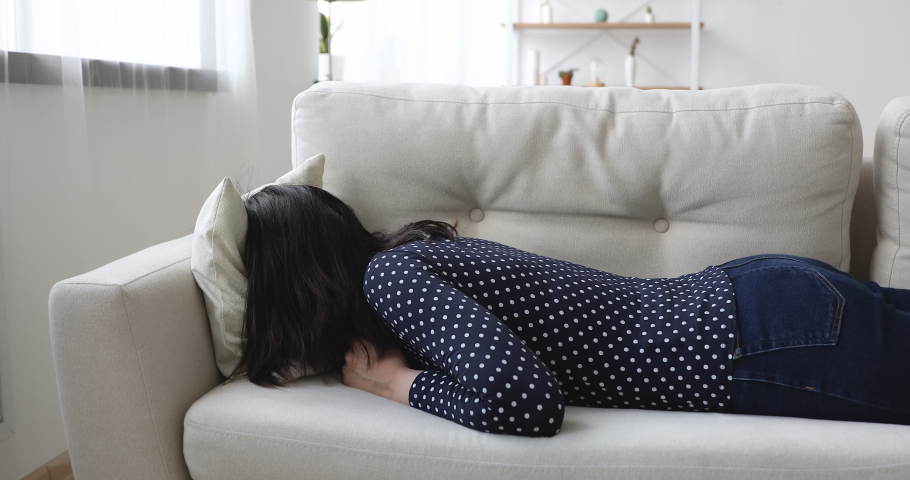 Exhausted young woman flopped down on sofa face in cushion rest in living room. Concept of tired overworked person hard day, teen girl first unrequited love life troubles, lack of energy breakdown Royalty-Free Stock Footage #1055094482