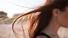 Close back view of brown woman hair tender movement in the air in slow motion 120 fps. Brunette woman in sunglasses walking on sandy beach. Wind blows airy hair shining in sun on sunset. Macro video.