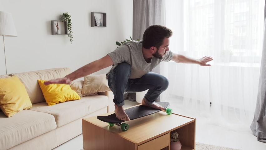 Modern man spending lockdown time at home practicing skateboard balancing on coffee table in living room Royalty-Free Stock Footage #1055095010