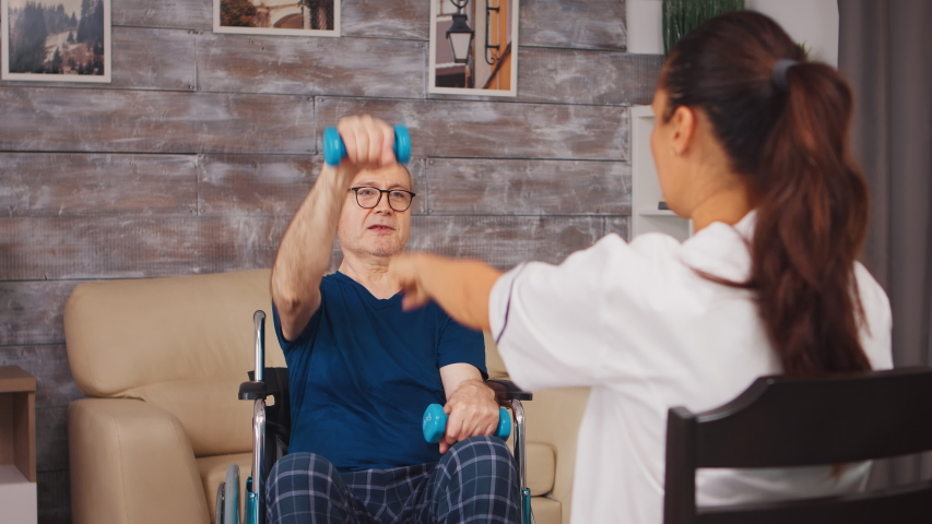 Senior man physiotherapy in wheelchair with help from medical worker. Disabled handicapped old person with social worker in recovery support therapy physiotherapy healthcare system nursing retirement