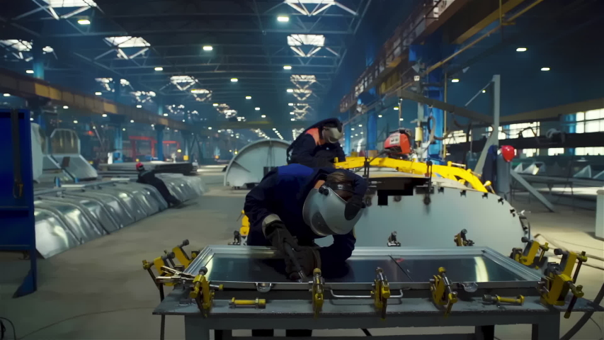 Factory Worker at Advanced Factory of railcar manufacturer train production plant, wide cinematic shot, dolly out | Shutterstock HD Video #1055097326