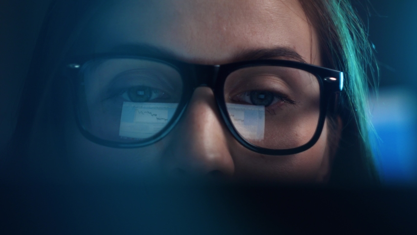 Close up of tired woman working at night on laptop, girl in eye glasses with reflections overworking busy, using computer in dark office