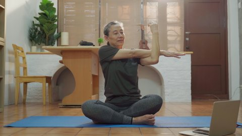 Senior Asia woman exercise and stretching yoga pose at home