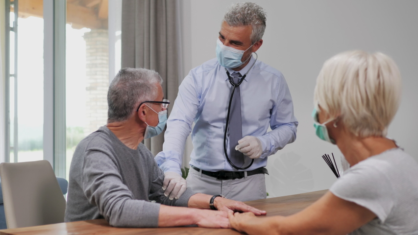 doctor with protective mask visit elderly man in quarantine at home during coronavirus covid-19 pandemic,health check up talking to old senior patient greeting with an elbow bump social distancing Royalty-Free Stock Footage #1055105876