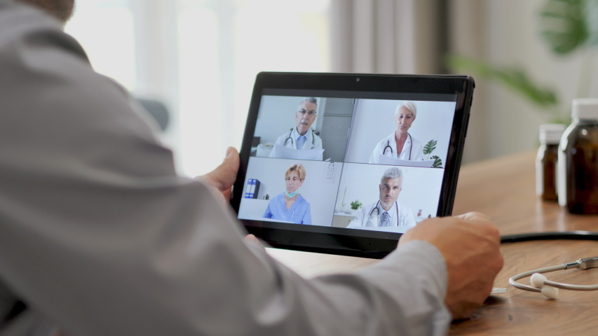 Doctor in self isolation remote working from home,having a video call conference with colleagues online,medical workteam discussing on livestream chat using tablet | Shutterstock HD Video #1055105885
