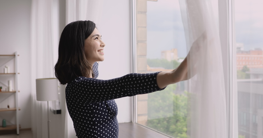 Vietnamese ethnicity young woman come to window in cozy modern living room opens curtains breathes fresh air-conditioned air admires view dreams of the future enjoys morning starting new day concept Royalty-Free Stock Footage #1055106488