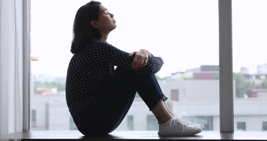 Side view sad Vietnamese woman sitting on windowsill embraces laps feels unhappy, lost on unpleasant thoughts, suffering due life troubles, break up or divorce, waiting or missing beloved man concept Royalty-Free Stock Footage #1055106491