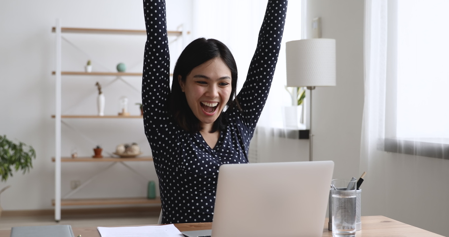 Happy asian young woman sit at desk at home or workplace typing on laptop receive great news celebrating moment of victory, personal achievement, got hired, high school scholarship admission concept Royalty-Free Stock Footage #1055106539