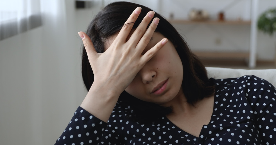 Close up view vietnamese young woman sitting on sofa alone feels depressed looking unhappy suffers having mental pain goes through divorce cheated by boyfriend, unwell bad condition, break up concept Royalty-Free Stock Footage #1055106569