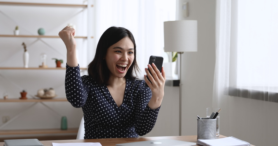 Asian woman sit at desk hold cellphone typing message receive sms from bank feels incredible happy. Girl makes yes I did it gesture look very excited. Achievement, got hired, lottery money win concept | Shutterstock HD Video #1055106719