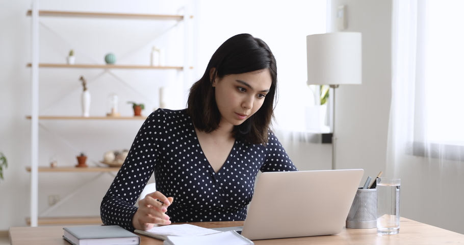 Asian student woman sitting at desk looking at computer screen makes notes studying prepare essay using on-line internet website, search information prepares for college exams, self-education concept Royalty-Free Stock Footage #1055106737