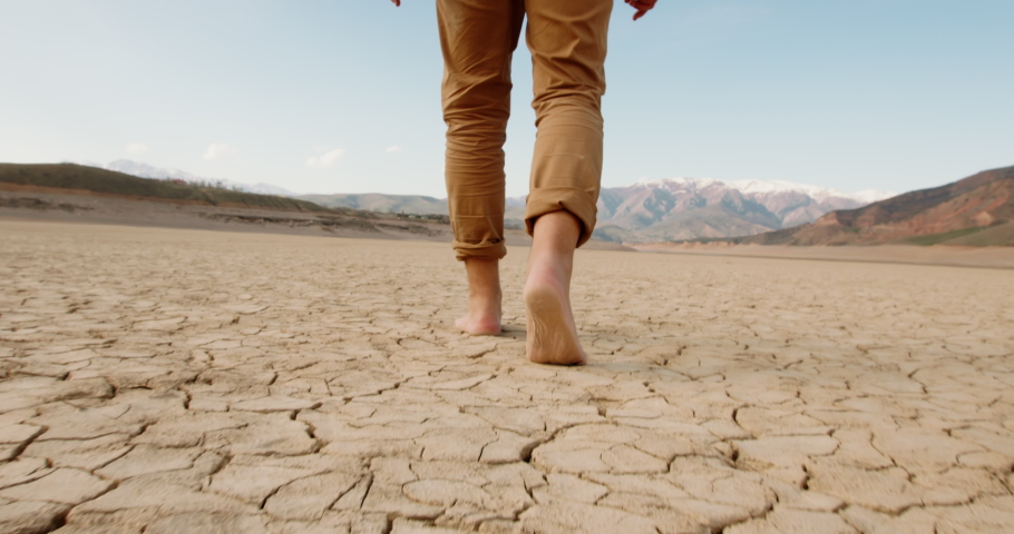 Close up shot of feet of adult man walking barefoot on bottom of dried lake or river, stepping on cracked soil ground destroyed by erosions - ecological issues concept 4k footage Royalty-Free Stock Footage #1055107598