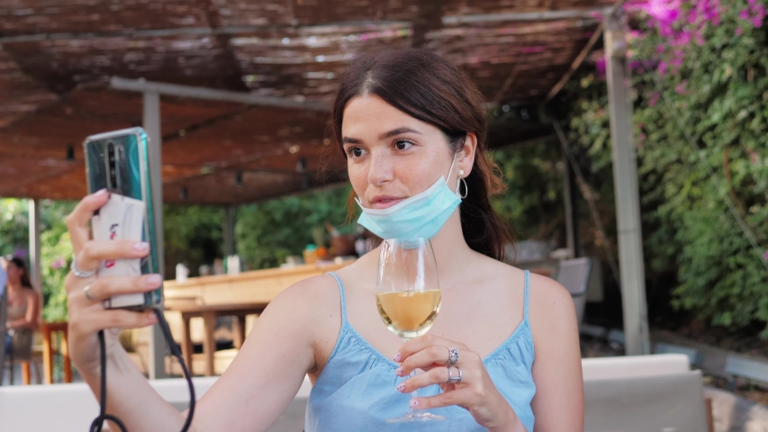 Girl wear surgical protective face mask sitting in outdoor cafe with cold drink alone and social distancing, lifestyle during covid-19 pandemic, video chat conference selfie   Shutterstock HD Video #1055111879