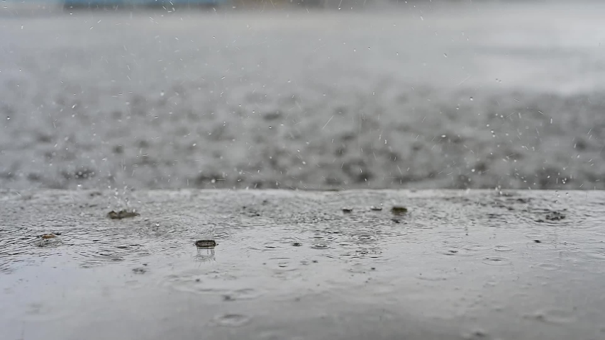 Slow Motion, rain water drops falling into big puddle on asphalt, flooding the street. Road floods due to the heavy rain in wet season. Raindrops falling down