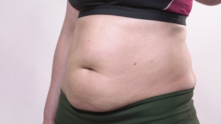 A middle-aged woman with saggy skin shakes a big belly, on a white background. Side plan. | Shutterstock HD Video #1055116784