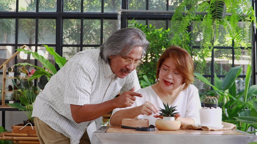 Elderly Asian couple are happily looking after the trees in the garden at home. The concept of living on vacation with happiness in nature | Shutterstock HD Video #1055117366