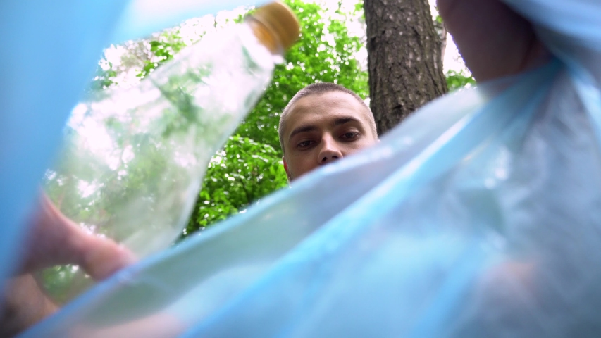 A young Caucasian man with a beard puts a plastic bottle in a trash bag. The view from the bag. Garbage collection in the forest. | Shutterstock HD Video #1055117408