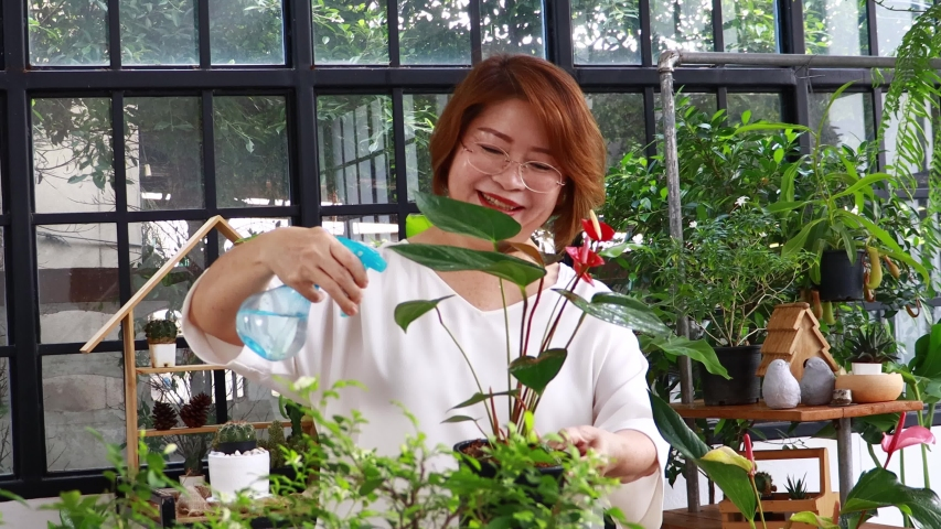 Elderly Asian woman are watering and looking after the trees in the garden at home happily during the holidays. The concept of living on vacation with happiness in nature | Shutterstock HD Video #1055117435