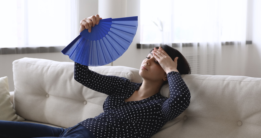 Unhealthy young Vietnamese woman sit leaned on couch at home waves blue waver fan reduce heat feels unwell. Sick millennial girl rest on sofa, suffering from sun stroke or hormonal imbalance concept