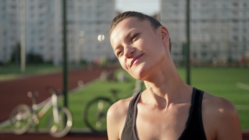 A beautiful young woman in sportswear stretches on a street sports field. It warms the muscles of the neck. Active lifestyle and sports outdoor.   Shutterstock HD Video #1055119727