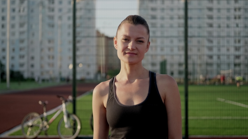 A young beautiful caucasian brunette woman poses in sportswear against the background of the sports ground. Active lifestyle. Evening light and sunset.   Shutterstock HD Video #1055119730