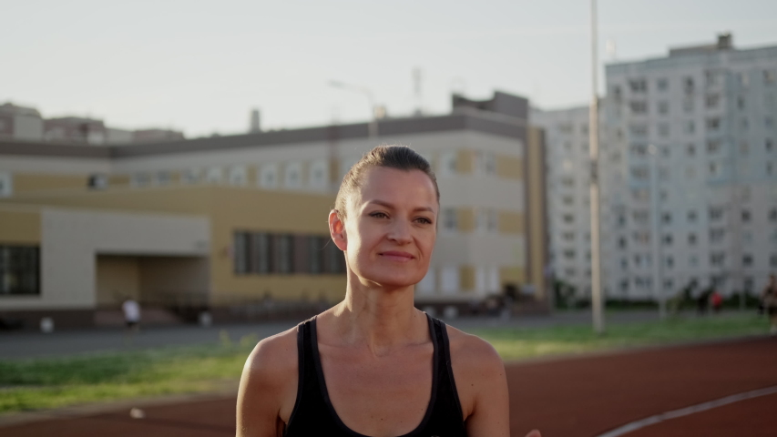 A beautiful young woman in sportswear is running on the treadmill of the stadium. Jogging at sunset, summer evening. Active lifestyle.   Shutterstock HD Video #1055119733