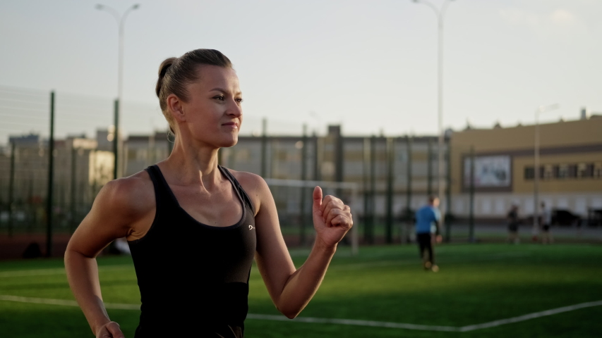 A beautiful young woman in sportswear is running on the treadmill of the stadium. Jogging at sunset, summer evening. Active lifestyle.   Shutterstock HD Video #1055119742