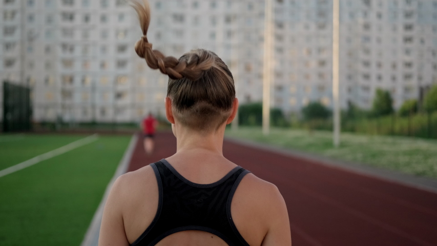 A beautiful young woman in sportswear is running on the treadmill of the stadium. Jogging at sunset, summer evening. Active lifestyle.   Shutterstock HD Video #1055119745