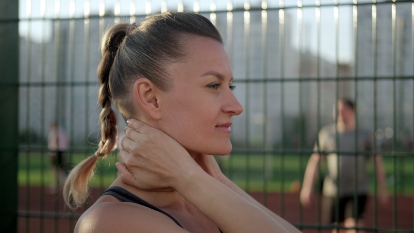 A beautiful young woman in sportswear stretches on a street sports field. It warms the muscles of the neck. Active lifestyle and sports outdoor.   Shutterstock HD Video #1055119763