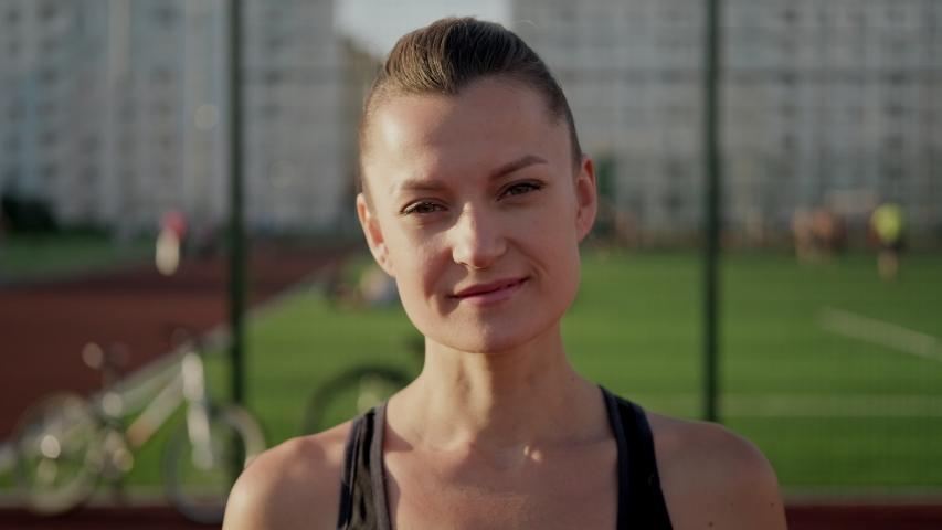 A young beautiful caucasian brunette woman poses in sportswear against the background of the sports ground. Active lifestyle. Evening light and sunset.   Shutterstock HD Video #1055119778