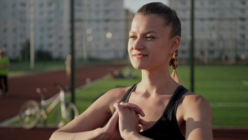 A beautiful young woman in sportswear stretches on a street sports field. It warms the muscles of the neck. Active lifestyle and sports outdoor.   Shutterstock HD Video #1055119790