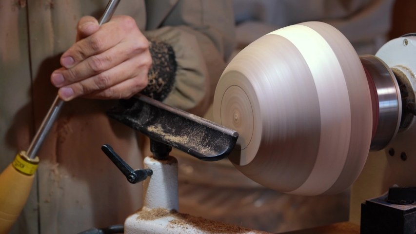 Craftsman works with workpiece in authentic workshop. Woodworker handles wood by bench. Making beautiful wooden handmade dish. Creation of unusual plate. Carpenter cuts wood by graver in soft focus | Shutterstock HD Video #1055120201