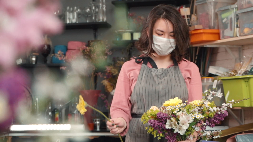 Female adding new flower to bouquet. asian woman florist holding a half made arrangement and adding plants to composition. wearing mask due to flu. Designing, floral workshop, working concept | Shutterstock HD Video #1055123156